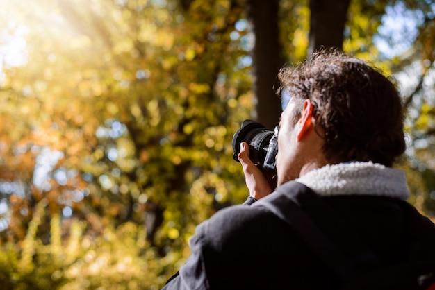 Fotograaf fotograferen in herfst bos tegen fel zonlicht