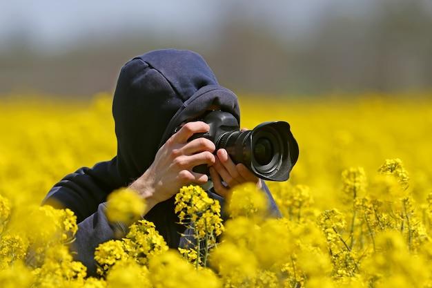 Fotograaf geschoten met een camera in zijn handen zittend in een veld met bloeiende koolzaad.