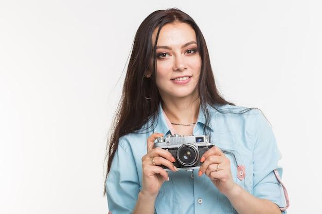 Fotograaf, hobby en mensen concept - jonge brunette vrouw met retro camera op witte achtergrond.