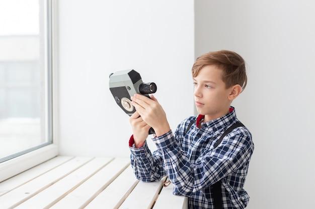 Fotograaf, kinderen en hobbyconcept - het leuke tienerjongen stellen met retro camera op witte muur