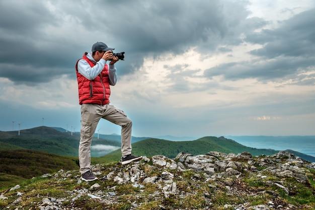 Fotograaf maakt een foto van een landschap in de bergen