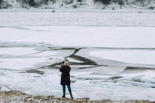 Fotograaf maakt foto's bevroren helder ijs in de winterrivier.