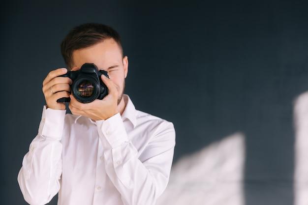 Fotograaf maakt foto's met dslr-camera en knippert met de ogen