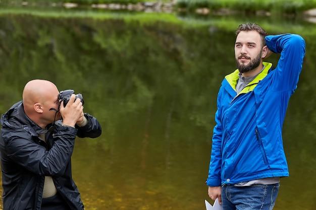 Fotograaf maakt foto's op mannelijk model in de natuur.