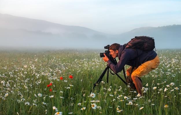Fotograaf maakt foto's van een veld met kamilles tijdens zonsopgang