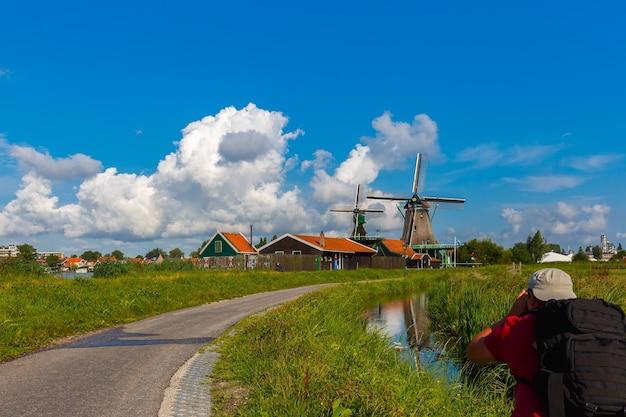 Fotograaf maakt pittoresk landelijk landschap met windmolens in de zaanse schans dicht bij de rivier