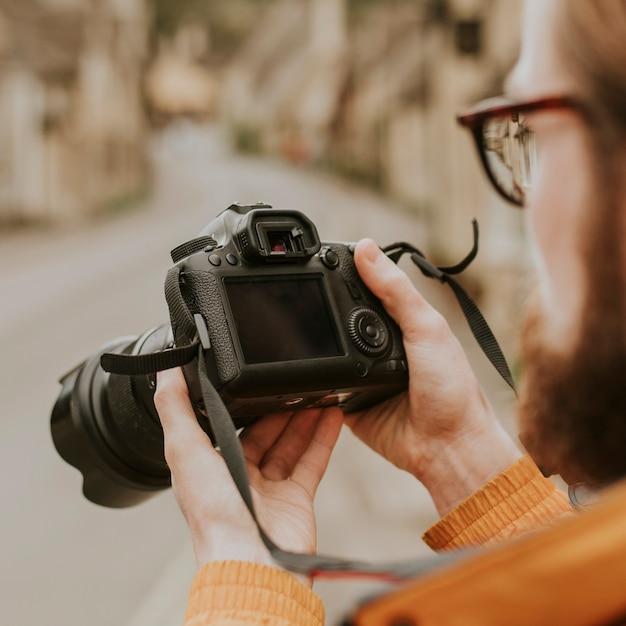 Fotograaf man die zijn foto's op de camera bekijkt