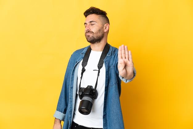Fotograaf man geïsoleerd op gele achtergrond stop gebaar maken en teleurgesteld
