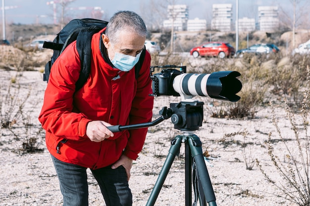 Fotograaf met chirurgisch masker fotograferen en video op straat met behulp van een statief