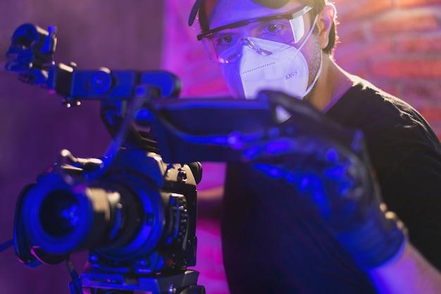 Fotograaf met kn95-masker met een professionele camera achter de schermen van videoproductie, coronavirusbeschermingsconcept