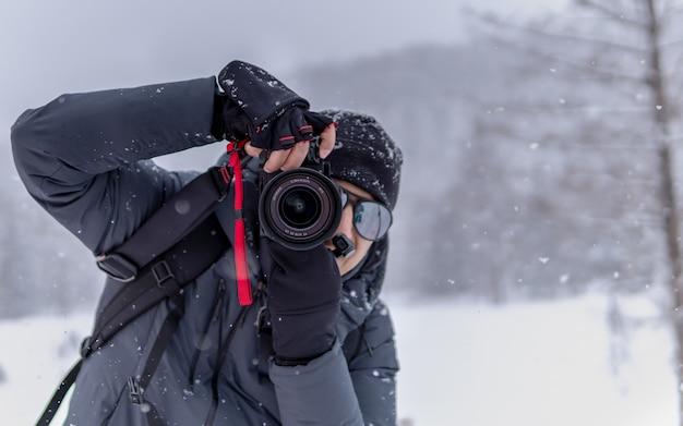 Fotograaf met vallende sneeuw achtergrond