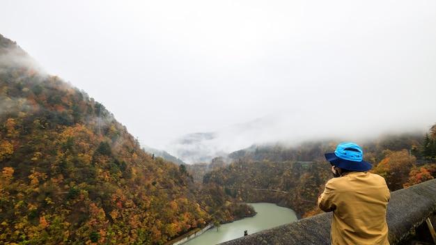 Fotograaf neemt foto van berg over vallei met herfstbladeren en mist in japan.
