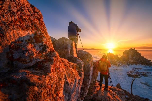 Fotograaf neemt foto van shamanka-rots bij zonsondergang met natuurlijk brekend ijs in bevroren water op het baikalmeer, siberië, rusland.