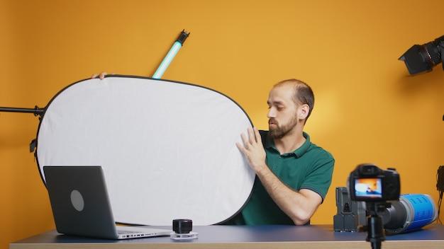 Fotograaf neemt vlog op over witlichtreflector in studio. professionele studiovideo- en fotoapparatuurtechnologie voor werk, fotostudio social media ster en influencer