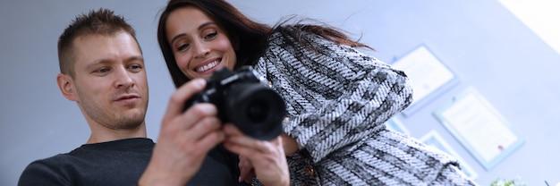 Fotograaf op kantoor toont fotomodel in camera. consultant past activiteiten bedrijf als geheel aan. fotosessie medewerkers op de werkplek. manager goed uitgevoerd project. foto's beste medewerkers bedrijf