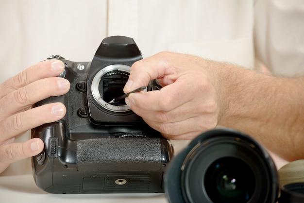 Fotograaf schoonmakende sensor van zijn camera