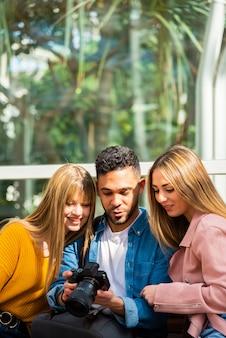 Fotograaf toont zijn werk op zijn camera aan twee jonge meisjes die op een bankje zitten