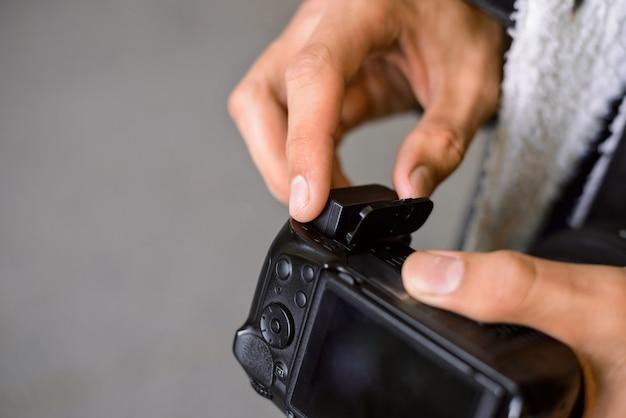 Fotograaf veranderende batterij in zijn dslr camera buitenshuis tijdens het fotograferen