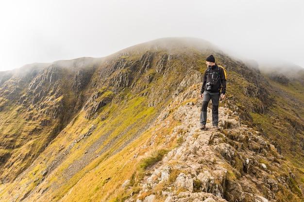 Fotograaf wandelen en kijken naar panorama op de top van de berg
