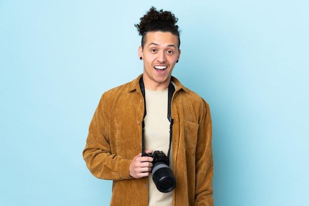 Fotograafmens over geïsoleerde blauwe achtergrond met verrassingsgelaatsuitdrukking