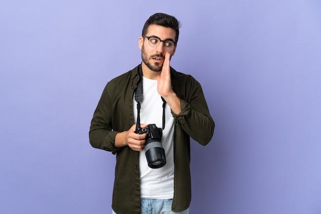 Fotograafmens over geïsoleerde paarse muur die iets met verrassingsgebaar fluistert terwijl hij opzij kijkt