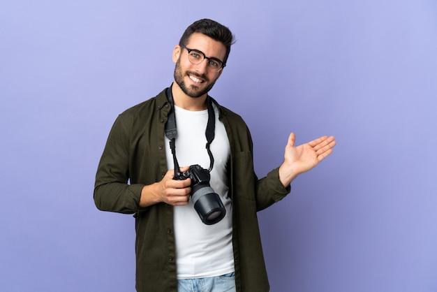 Fotograafmens over geïsoleerde purpere muur die een idee voorstelt terwijl het kijken glimlachen naar