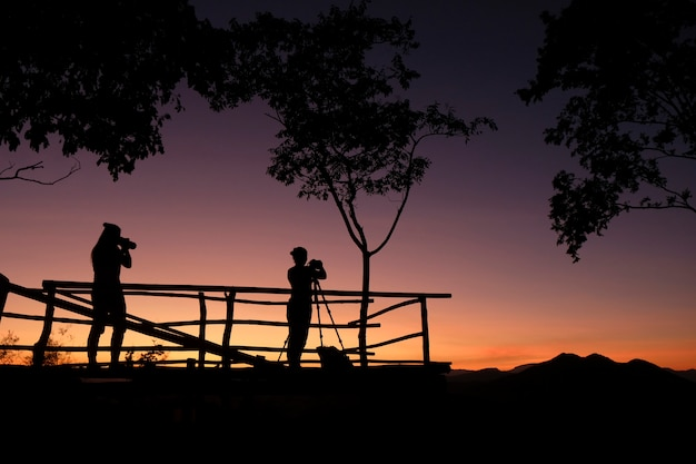 Fotograafsilhouet op de berg die foto schieten landschap met zonsondergang of zonsopgang - fotograafvrouw met camera