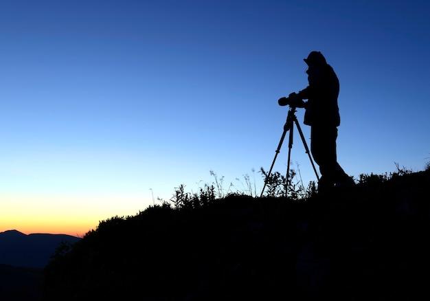 Fotograafsilhouet tegen de rijzende zon in de bergen