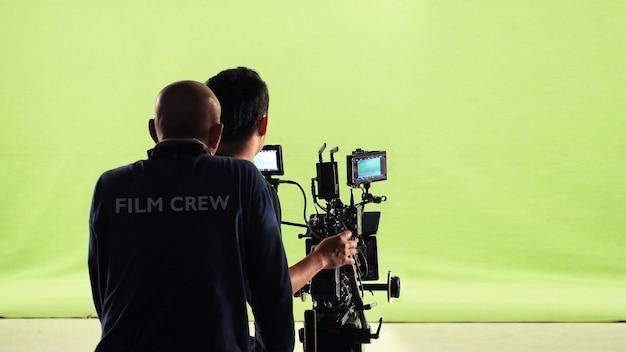 Fotograafteam en filmploeg en high definition online videocamera en groen schermachtergrond voor het maken van filmopnamen in grote studio.
