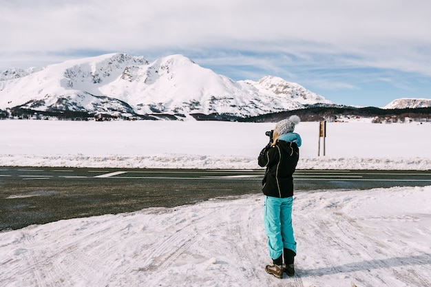Fotograafvrouw fotografeert een besneeuwde berg. hoge kwaliteit foto