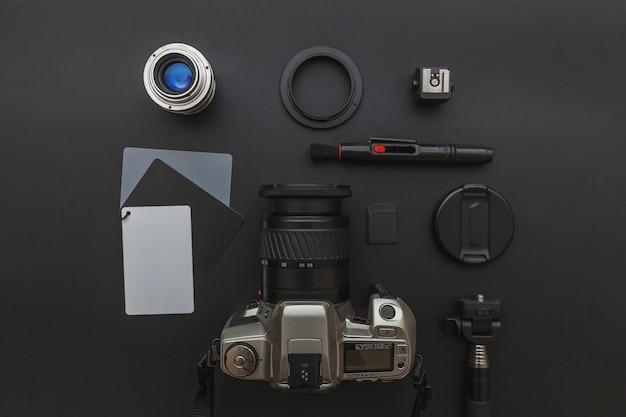 Fotograafwerkplek met dslr-camerasysteem, camera-reinigingsset, lens en camera-accessoire op donkere zwarte achtergrond