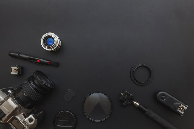 Fotograafwerkplek met dslr-camerasysteem, camera-reinigingsset, lens en camera-accessoire