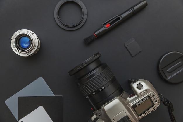 Fotograafwerkplek met dslr-camerasysteem en cameratoebehoren op zwarte achtergrond