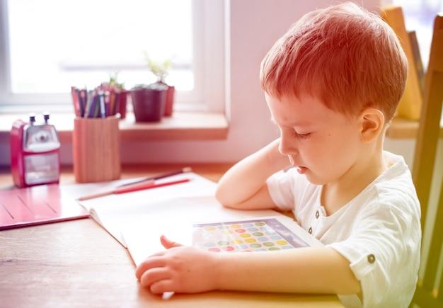 Fotogradiëntstijl met zoonjongen die een techneut digitaal apparaat speelt