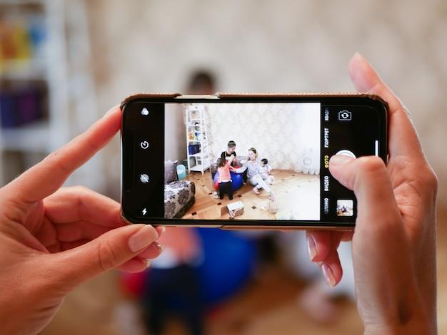 Fotografeert een gezin aan de telefoon. telefoon voorgrond. groep kleine vrienden en het nemen van selfie met smartphone op poef