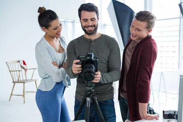 Fotografen en model beoordelen gemaakte foto's in zijn digitale camera