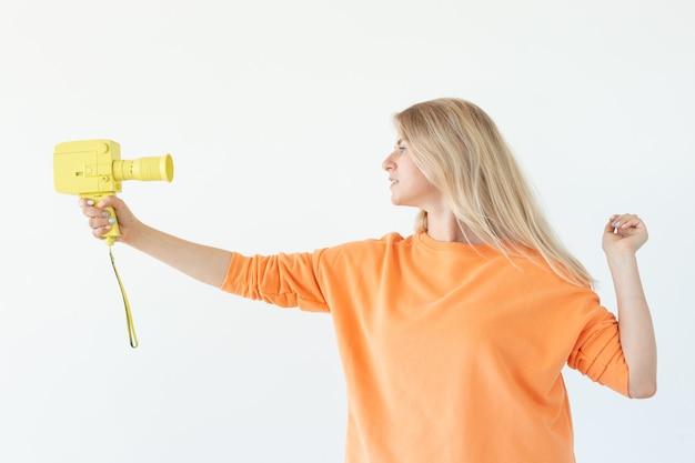 Fotograferen, emoties en vintage concept - jonge verrast vrouw met retro camera over de witte muur.