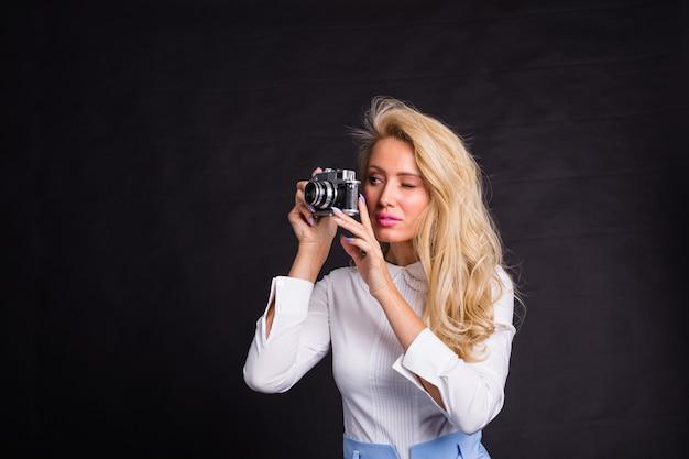 Fotograferen, mode en - jonge blonde vrouw die een foto maakt