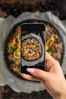 Fotograferen van voedselconcept - vrouw neemt foto van italiaanse pizza met zwart deeg en zeevruchten op een bakplaat uit de oven. fotograferen op een mobiele telefoon of tablet