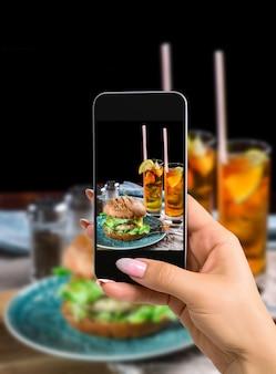 Fotograferen van voedselconcept vrouw neemt foto van sandwich met kipburger, kaas en sla