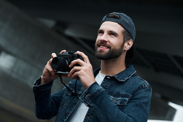 Fotografie hobby jonge stijlvolle man die op straat in de stad staat en foto's maakt op de camera die ernaar uitkijkt