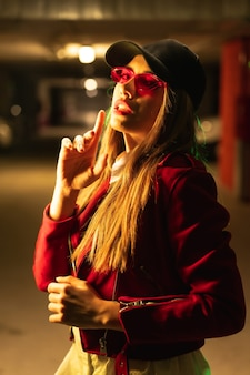 Fotografie met rode en groene neons op een parkeerplaats. jonge vrij blonde blanke vrouw in een rood pak, zonnebril en een zwarte pet