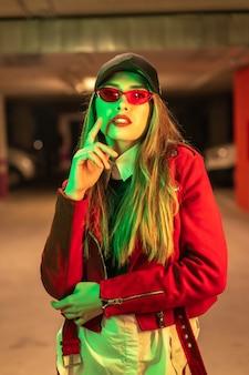Fotografie met rode en groene neons op een parkeerplaats. portret van een jonge vrij blonde blanke vrouw in een rood pak, zonnebril en een zwarte pet