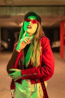 Fotografie met rode en groene neons op een parkeerplaats. portret van een jonge vrij blonde kaukasische vrouw in een rood kostuum en zonnebril