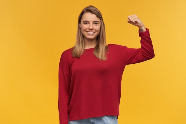 Fotografie van een sterk glimlachend blond jong meisje, stralend van geluk, toont haar spieren, haar kracht, houdt één hand gebogen en houdt een gebalde vuist vast