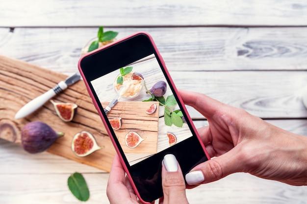 Fotografie van een vijg met ricotta op de mobiele telefoon