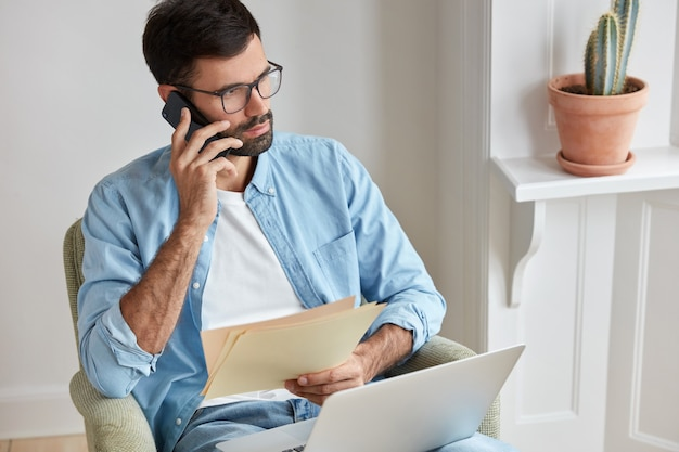 Fotografie van serieuze ondernemer hoort over realisatie van zijn bedrijf, voert telefoongesprek met assistent