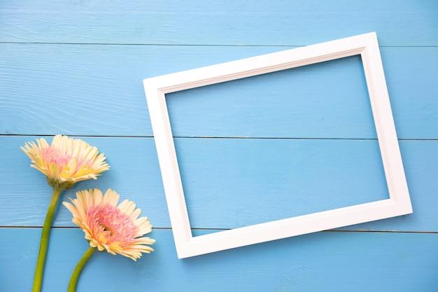 Fotokader en gele bloem op heldere blauwe houten achtergrond met bloemblaadjes. zomer plat leggen.