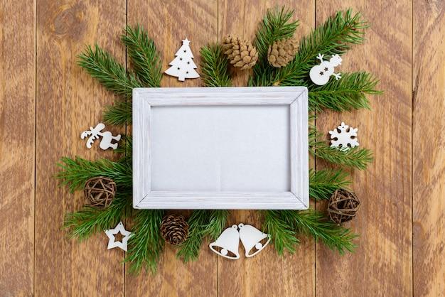 Fotokader tussen kerstdecoratie, met figuren en dennenappels op een bruine houten tafel. bovenaanzicht, frame om ruimte te kopiëren