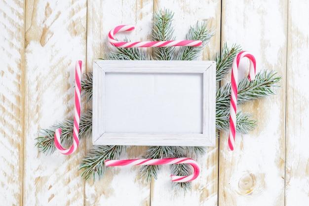 Fotokader tussen kerstmisdecoratie, met suikergoedriet op een witte houten lijst. bovenaanzicht, frame om ruimte te kopiëren